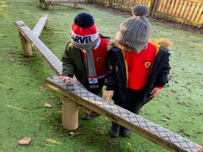 Reception children exploring in Forest School